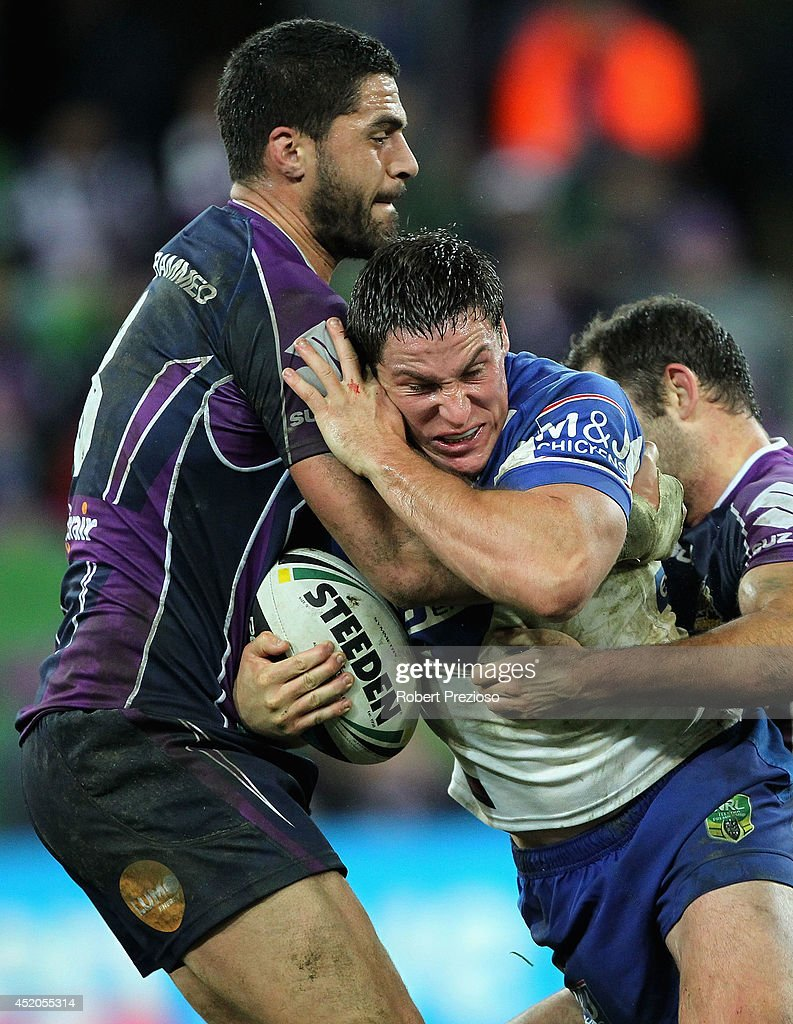 Josh Jackson of the Bulldogs is tackled by Jesse Bromwich of the Storm during the round 18 NRL match between the Melbourne Storm and the Canterbury...