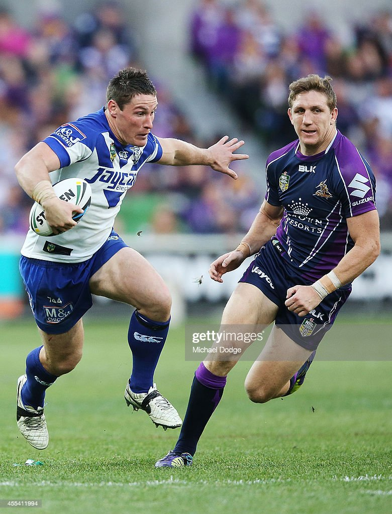 Josh Jackson of the Bulldogs runs with the ball away from Ryan Hoffman of the Storm during the NRL 2nd Elimination Final match between the Melbourne...