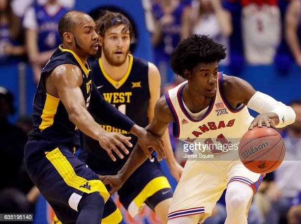 Josh Jackson of the Kansas Jayhawks controls the ball as Jevon Carter and Nathan Adrian of the West Virginia Mountaineers defend during the game at...