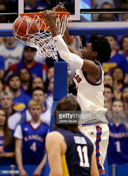 Josh Jackson of the Kansas Jayhawks dunks as Nathan Adrian of the West Virginia Mountaineers watches during the game at Allen Fieldhouse on February...
