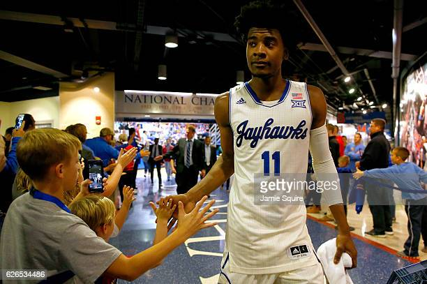 Josh Jackson of the Kansas Jayhawks highfives kids as he walks off the court following the game against the Long Beach State 49ers at Allen...