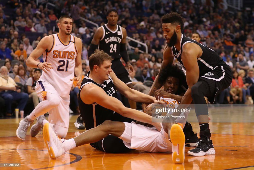 Josh Jackson #20 of the Phoenix Suns battles for a loose ball with Timofey Mozgov #20 and Allen Crabbe #33 of the Brooklyn Nets during the first half of the NBA game at Talking Stick Resort Arena on November 6, 2017 in Phoenix, Arizona.