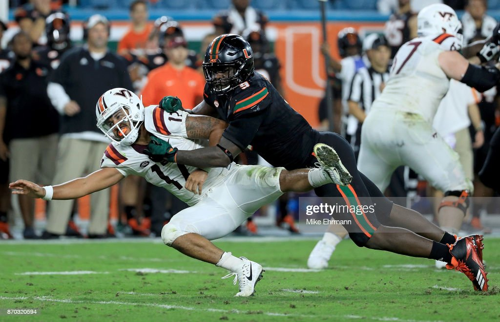 Josh Jackson #17 of the Virginia Tech Hokies is tackled by Chad Thomas #9 of the Miami Hurricanes during a game at Hard Rock Stadium on November 4, 2017 in Miami Gardens, Florida.