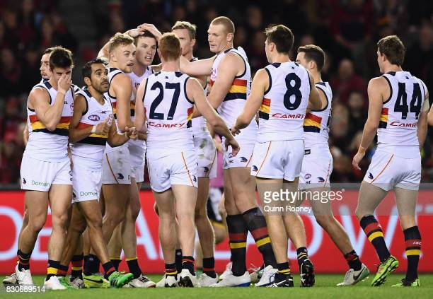 Josh Jenkins of the Crows is congratulated by team mates after kicking a goal during the round 21 AFL match between the Essendon Bombers and the...
