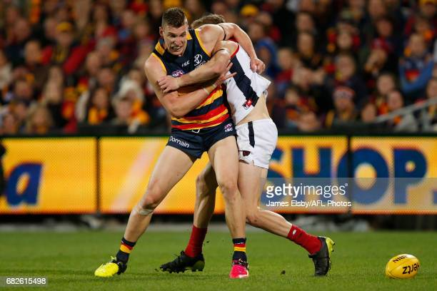 Josh Jenkins of the Crows is tackled by Sam Frost of the Demons during the 2017 AFL round 08 match between the Adelaide Crows and the Melbourne...