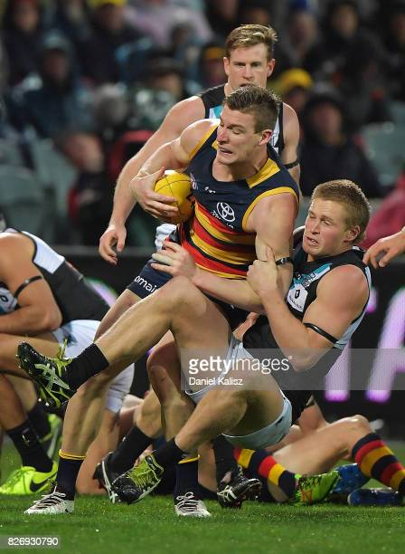 Josh Jenkins of the Crows is tackled by Tom Clurey of the Power during the round 20 AFL match between the Adelaide Crows and the Port Adelaide Power...