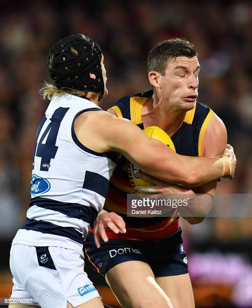 Josh Jenkins of the Crows is tackled by Tom Stewart of the Cats during the round 18 AFL match between the Adelaide Crows and the Geelong Cats at...