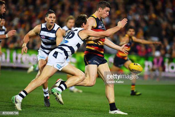 Josh Jenkins of the Crows kicks the ball through for a goal as Mark Blicavs of the Cats attempts to tackle during the round 18 AFL match between the...