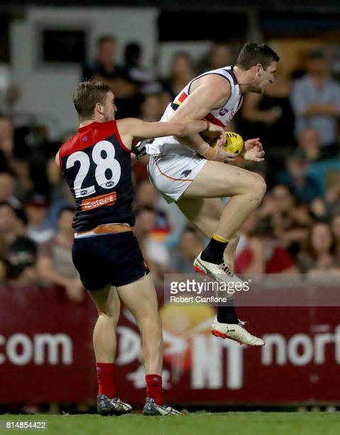 Josh Jenkins of the Crows marks in front of Oscar McDonald of the Demons during the round 17 AFL match between the Melbourne Demons and the Adelaide...