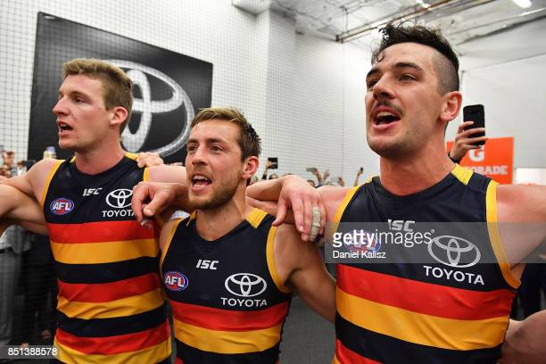 Josh Jenkins Richard Douglas and Taylor Walker of the Crows sing the club song after the First AFL Preliminary Final match between the Adelaide Crows...