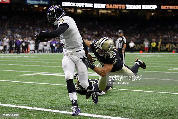 Josh Johnson of the Baltimore Ravens scores a touchdown as he is tackled by Erik Harris of the New Orleans Saints at the MercedesBenz Superdome on...