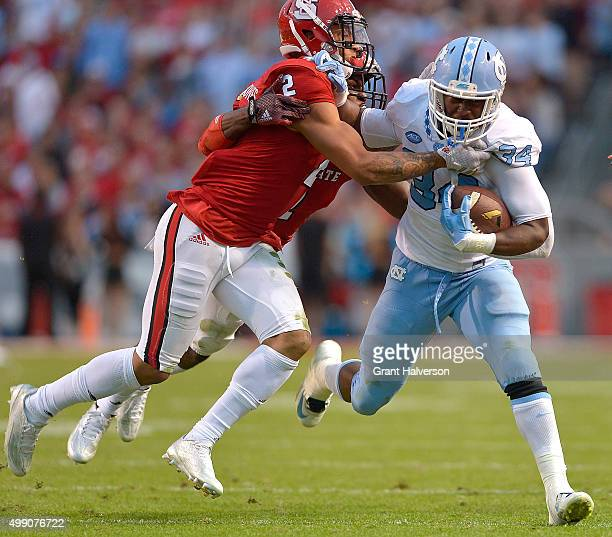 Josh Jones and Hakim Jones of the North Carolina State Wolfpack tackle Elijah Hood of the North Carolina Tar Heels during their game at CarterFinley...