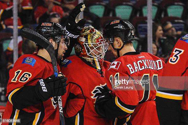 Josh Jooris Joni Ortio and Mikael Backlund of the Calgary Flames celebrate after defeating the Winnipeg Jets during an NHL game at Scotiabank...