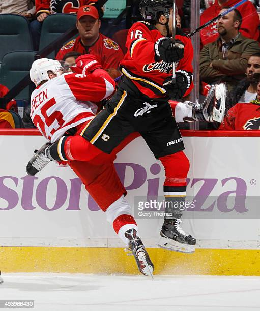 Josh Jooris of the Calgary Flames crashes into the boards against Mike Green of the Detroit Red Wings at Scotiabank Saddledome on October 23 2015 in...