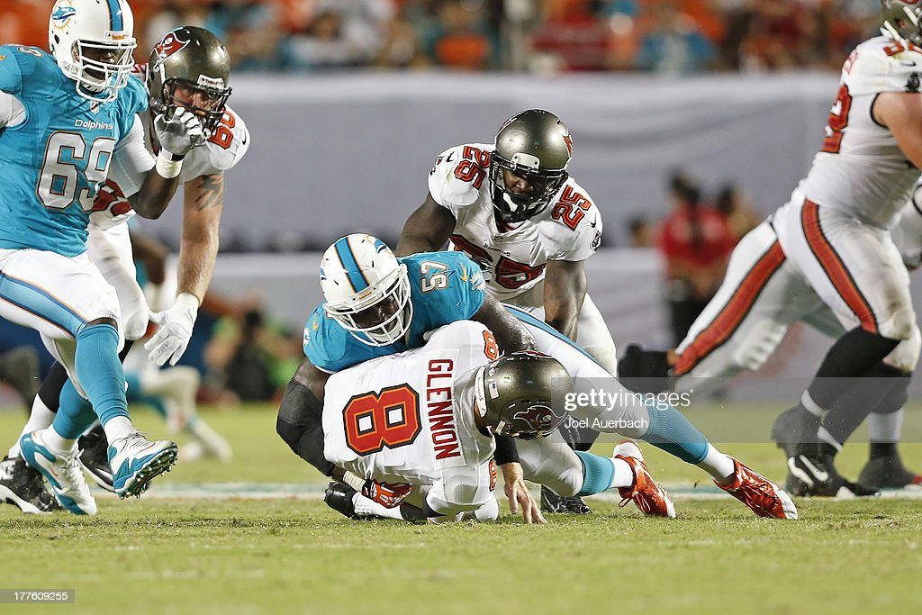 Josh Kaddu #57 of the Miami Dolphins sacks Mike Glennon #8 of the Tampa Bay Buccaneers during a preseason game on August 24, 2013 at Sun Life Stadium in Miami Gardens, Florida. The Buccaneers defeated the Dolphins 17-16.