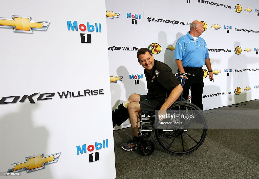 Josh Katz pushes the wheelchair of <a gi-track='captionPersonalityLinkClicked' href=/galleries/search?phrase=Tony+Stewart+-+Race+Car+Driver&family=editorial&specificpeople=201686 ng-click='$event.stopPropagation()'>Tony Stewart</a>, NASCAR Sprint Cup Series driver and co-owner of Stewart-Haas Racing, before he speaks to the media in his first appearance since his sprint car accident at Stewart-Haas Racing on September 3, 2013 in Kannapolis, North Carolina.