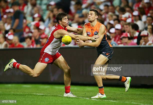 Josh Kelly of the Giants handballs under pressure from Craig Bird of the Swans during the round three AFL match between the Sydney Swans and the...