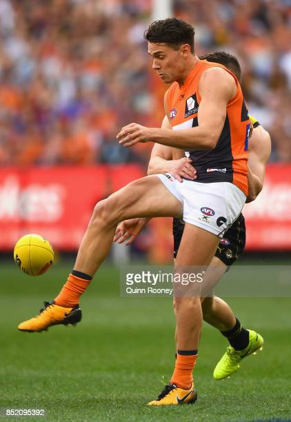 Josh Kelly of the Giants kicks whilst being tackled during the Second AFL Preliminary Final match between the Richmond Tigers and the Greater Western...