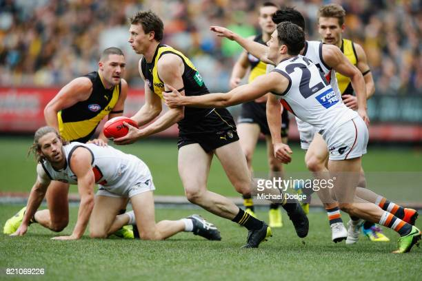 Josh Kelly of the Giants tackles Dylan Grimes of the Tigers during the round 18 AFL match between the Richmond Tigers and the Greater Western Sydney...