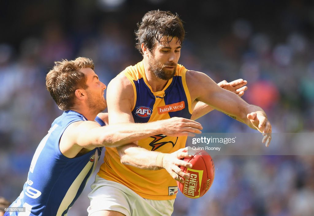 Josh Kennedy of the Eagles kicks whilst being tackled by Luke McDonald of the Kangaroos during the round one AFL match between the North Melbourne Kangaroos and the West Coast Eagles at Etihad Stadium on March 26, 2017 in Melbourne, Australia.