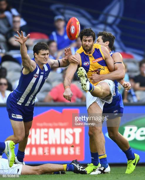 Josh Kennedy of the Eagles kicks whilst being tackled during the round one AFL match between the North Melbourne Kangaroos and the West Coast Eagles...