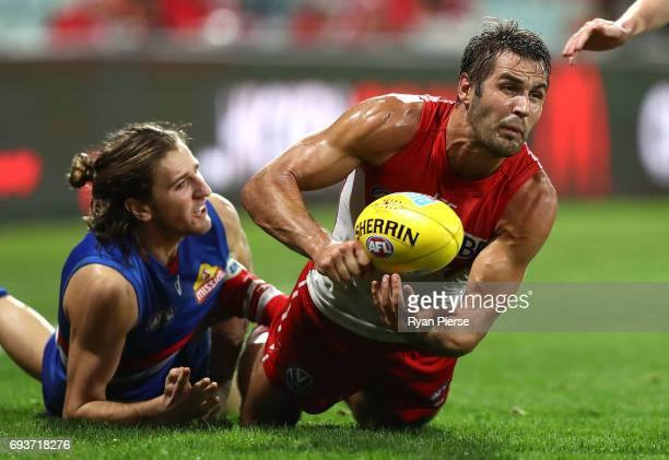 Josh Kennedy of the Swans gets a handball away despite pressure from Marcus Bontempelli of the Bulldogs during the round 12 AFL match between the...