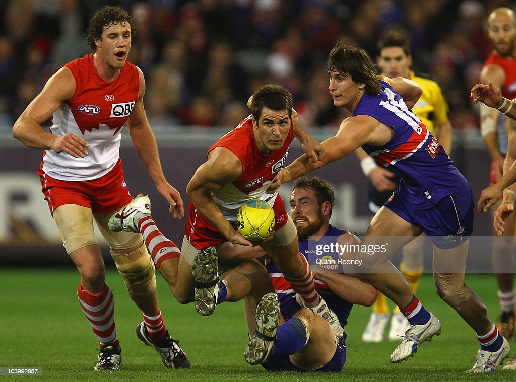 Josh Kennedy of the Swans handballs out of a pack whilst being tackled by Ben Hudson of the Bulldogs during the AFL First Semi Final match between the Western Bulldogs and the Sydney Swans at Melbourne Cricket Ground on September 11, 2010 in Melbourne, Australia.