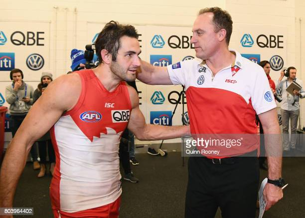 Josh Kennedy of the Swans is congratulated by Swans head coach John Longmire in the rooms after winning the round 15 AFL match between the Melbourne...
