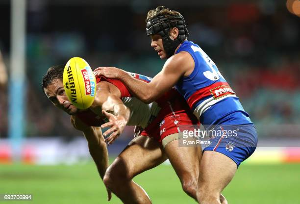 Josh Kennedy of the Swans is tackled by Caleb Daniel of the Bulldogs during the round 12 AFL match between the Sydney Swans and the Western Bulldogs...