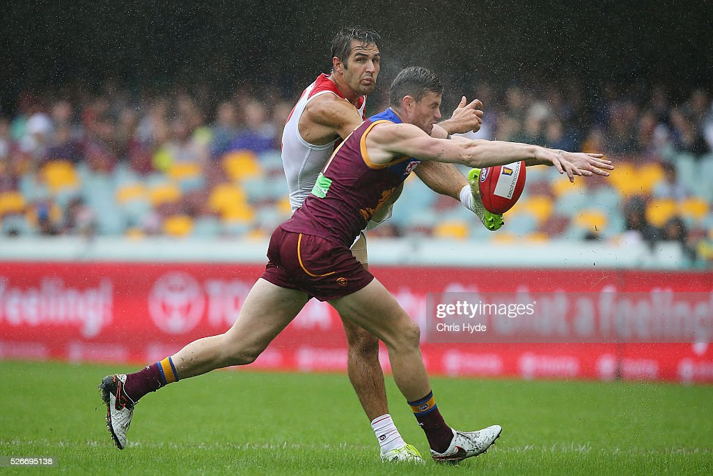 Josh Kennedy of the Swans kicks while Pearce Hanley of the Lions blocks the kick during the round six AFL match between the Brisbane Lions and the Sydney Swans at The Gabba on May 1, 2016 in Brisbane, Australia.
