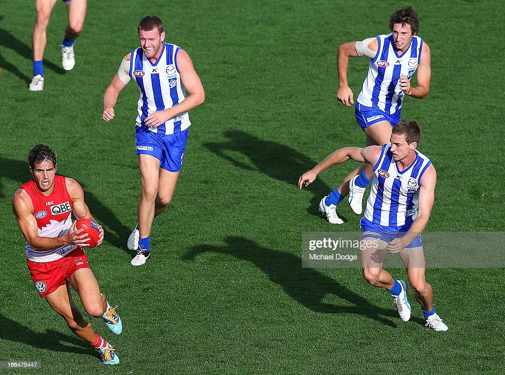 Josh Kennedy of the Swans runs away with the ball from Lachlan Hansen, Sam Wright and Shaun Atley of the Kangaroos during the round three AFL match between the North Melbourne Kangaroos and the Sydney Swans at Blundstone Arena on April 13, 2013 in Hobart, Australia.