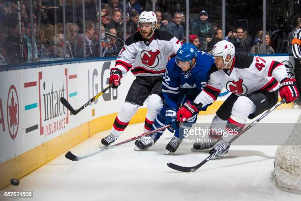 Josh Leivo of the Toronto Maple Leafs battles for the puck with Dalton Prout and Jon Merrill of the New Jersey Devils during the first period at the...