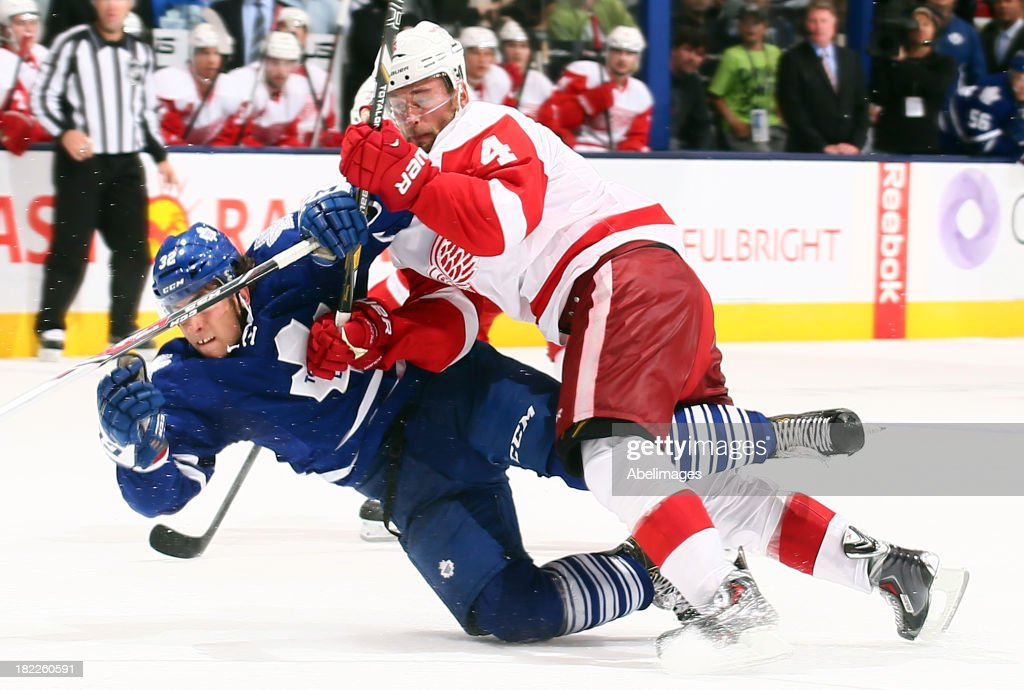 Josh Leivo #32 of the Toronto Maple Leafs gets hit by <a gi-track='captionPersonalityLinkClicked' href=/galleries/search?phrase=Jakub+Kindl&family=editorial&specificpeople=716743 ng-click='$event.stopPropagation()'>Jakub Kindl</a> #4 of the Detroit Red Wings during NHL Preseason action at the Air Canada Centre September 28, 2013 in Toronto, Ontario, Canada.