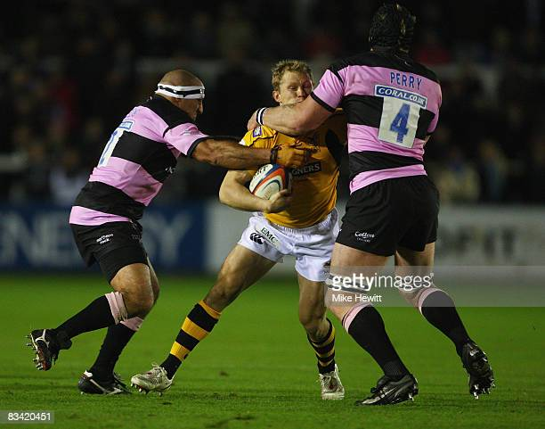 Josh Lewsey of Wasps is sandwiched by Andy Long and Andy Perry of Newcastle Falcond during the EDF Energy Cup match between Newcastle Falcons and...