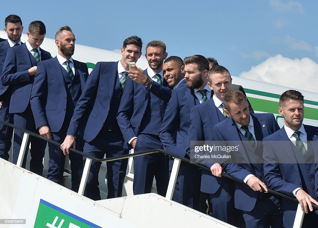 Josh Magennis (R) takes a selfie alongside Gareth McAuley (C) and Kyle Lafferty (L) as the Northern Ireland team pose for an official photograph before their training camp departure at George Best City Airport on May 30, 2016 in Belfast, Northern Ireland. Northern Ireland have qualified for the Euro 2016 football championship finals in France, the first time the province has qualified for an international football tournament final since 1986.