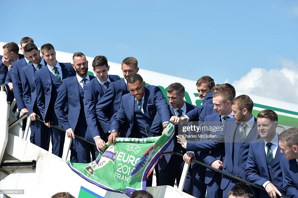 Josh Magennis unfurls a flag as the Northern Ireland team pose for an official photograph before their training camp departure at George Best City Airport on May 30, 2016 in Belfast, Northern Ireland. Northern Ireland have qualified for the Euro 2016 football championship finals in France, the first time the province has qualified for an international football tournament final since 1986.