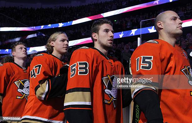 Josh Manson Hampus Lindholm Shea Theodore and Ryan Getzlaf of the Anaheim Ducks look on from the bench during the national anthem before the game...