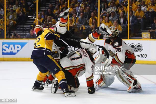 Josh Manson of the Anaheim Ducks falls over Mike Fisher of the Nashville Predators and Hampus Lindholm of the Anaheim Ducks during the third period...