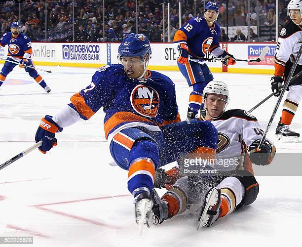 Josh Manson of the Anaheim Ducks trips up Anders Lee of the New York Islanders during the second period at the Barclays Center on December 21 2015 in...
