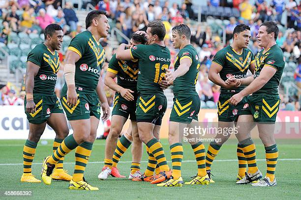 Josh Mansour of Australia celebrates scoring a try with team mates during the Four Nations match between the Australian Kangaroos and Samoa at WIN...