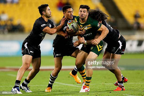 Josh Mansour of Australia is tackled by Shaun Johnson Dean Whare and Kevin Proctor of New Zealand during the Four Nations Final between the New...