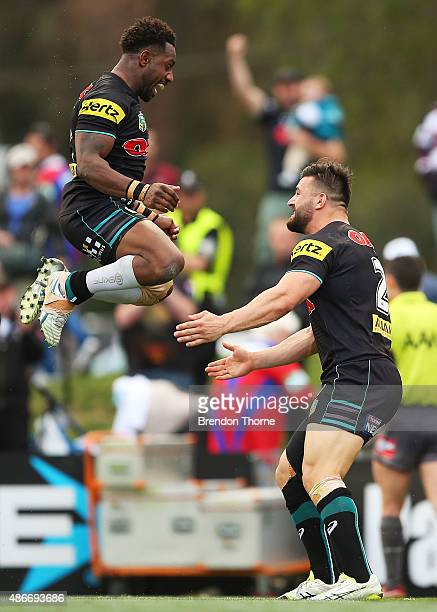 Josh Mansour of the Panthers celebrates with team mate James Segeyaro after scoring a try during the round 26 NRL match between the Penrith Panthers...