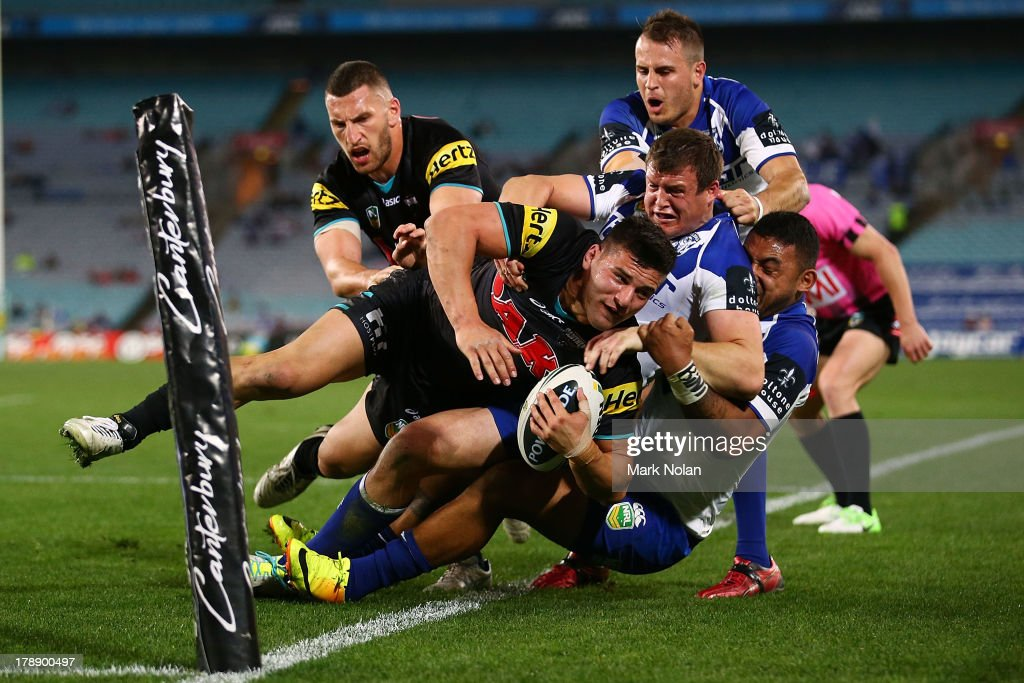 Josh Mansour of the Panthers is bundled into touch by the Bulldogs defence during the round 25 NRL match between the Canterbury Bulldogs and the Penrith Panthers at ANZ Stadium on August 31, 2013 in Sydney, Australia.