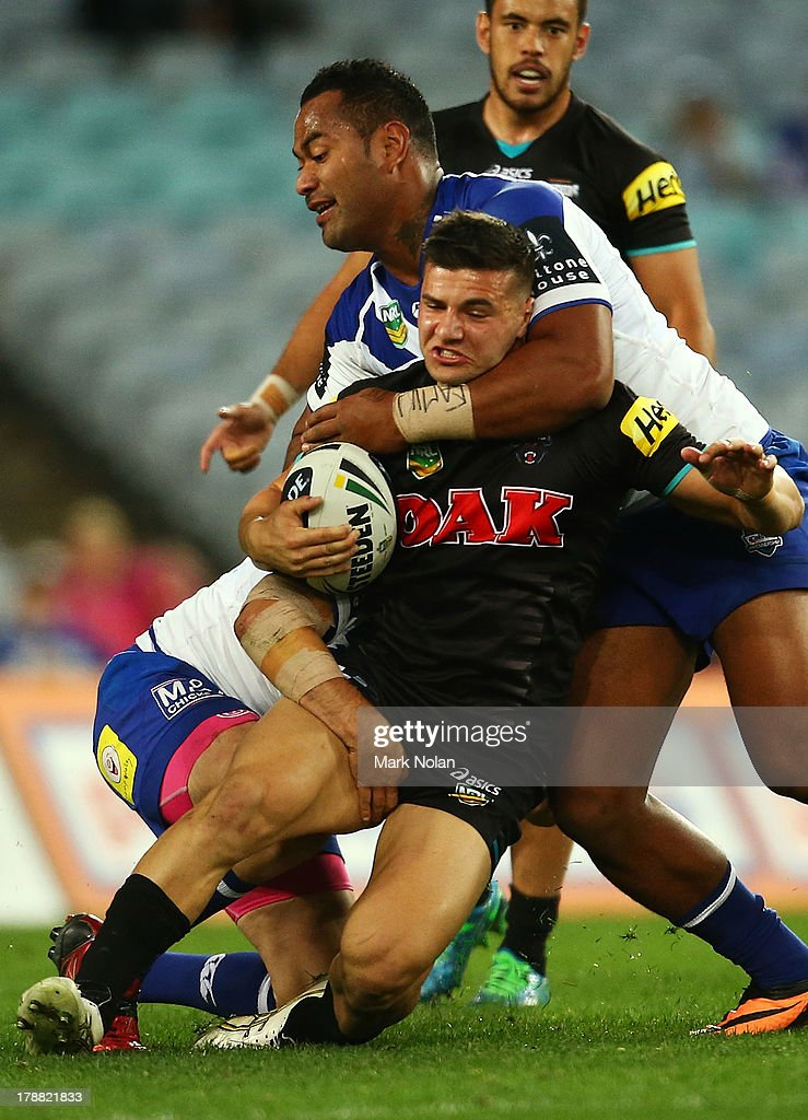 Josh Mansour of the Panthers is tacked high by Tony Williams of the Bulldogs during the round 25 NRL match between the Canterbury Bulldogs and the Penrith Panthers at ANZ Stadium on August 31, 2013 in Sydney, Australia.