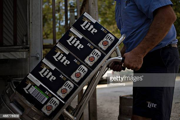 Josh McCartney a driver with Baumgarten Distributing Co moves cases of SABMiller Plc Miller Lite brand beer while making a delivery in Chillicothe...