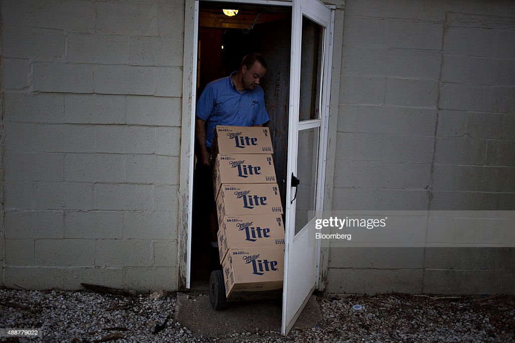 Josh McCartney a driver with Baumgarten Distributing Co moves cases of SABMiller Plc Miller Lite while making a delivery in Chillicothe Illinois US...