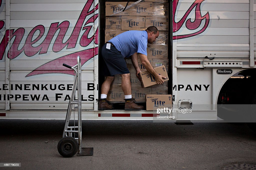 Josh McCartney a driver with Baumgarten Distributing Co stacks cases of SABMiller Plc Miller Lite while making a delivery in Chillicothe Illinois US...