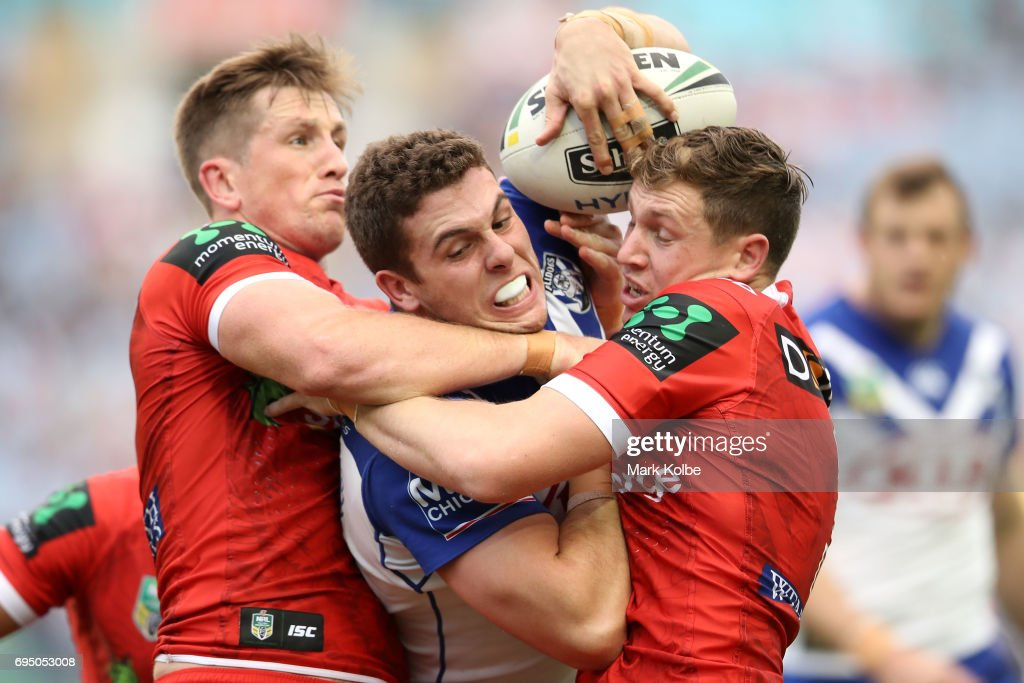 Josh McCrone (L) and Kurt Mann (R) of the Dragons tackle Adam Elliott (C) of the Bulldogs during the round 14 NRL match between the Canterbury Bulldogs and the St George Illawarra Dragons at ANZ Stadium on June 12, 2017 in Sydney, Australia.