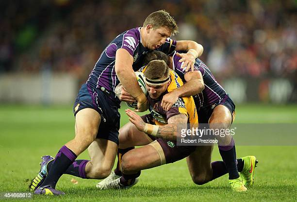Josh McGuire of the Broncos is tackled by Ryan Hoffman of the Storm during the round 26 NRL match between the Melbourne Storm and the Brisbane...