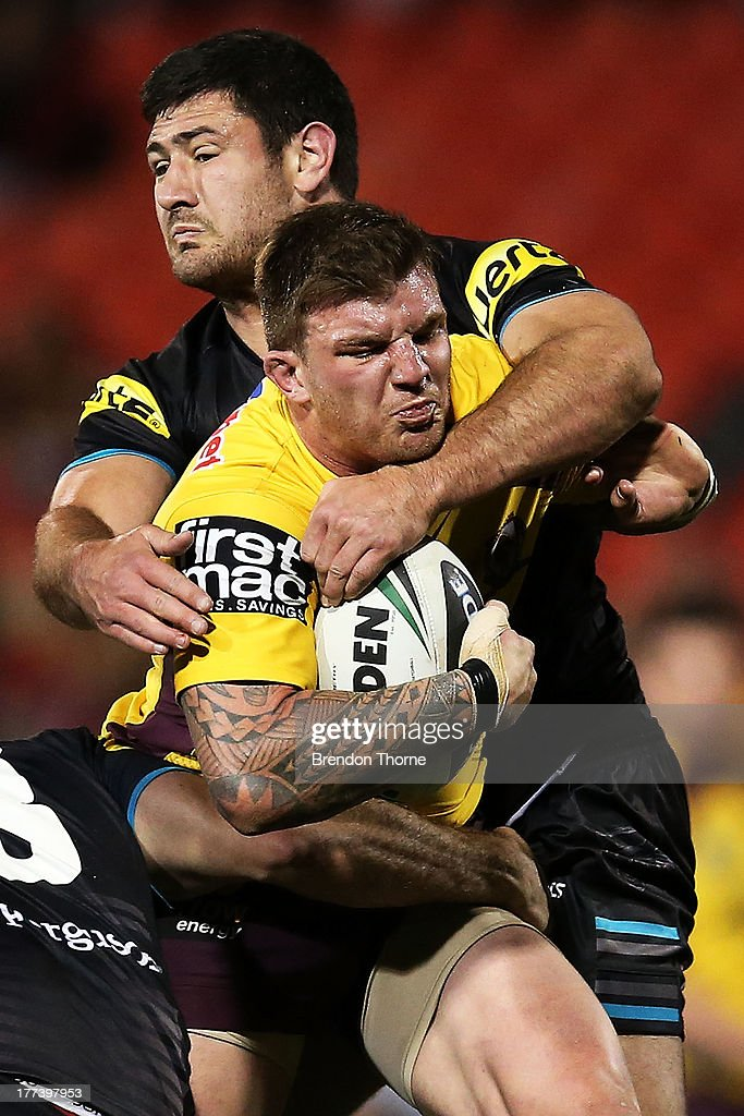 Josh McGuire of the Broncos is tackled by Sam McKendry of the Panthers during the round 24 NRL match between the Penrith Panthers and the Brisbane Broncos at Centrebet Stadium on August 23, 2013 in Sydney, Australia.